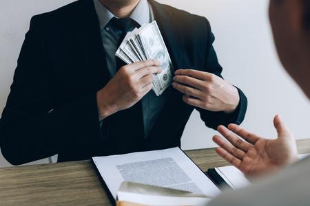 Businessman putting stack of money bills in his suit coat pocket. Foto de archivo - 115915656