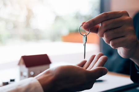 Close up hand of home agents are handing out keys to new home buyers.