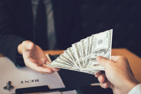 Salesman home brokers receive cash with buyers giving money for salesman.