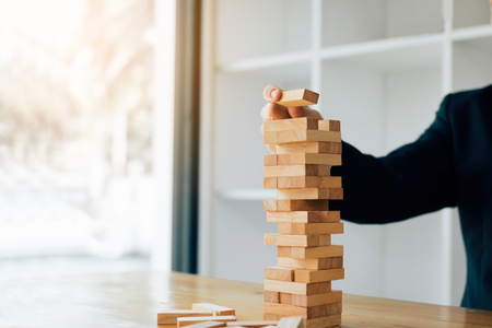 Hand of businessman playing wood blocks stacks game with planning strategy of project management.