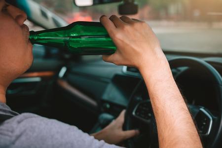 Chico asiático con alcohol borracho, bebiendo cerveza mientras conduce por la carretera. Foto de archivo
