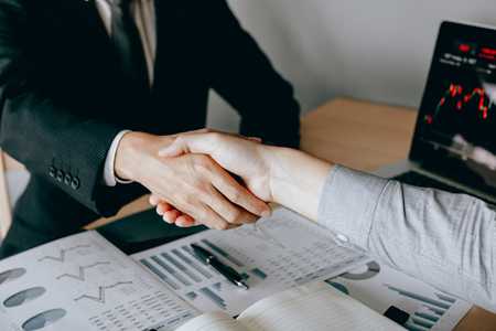 Two businessmen agreed to buy and sell shares by shaking hands in order to accept mutual investment.