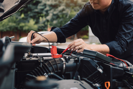 Car mechanic is using the car battery meter to measure various values and analyze it.