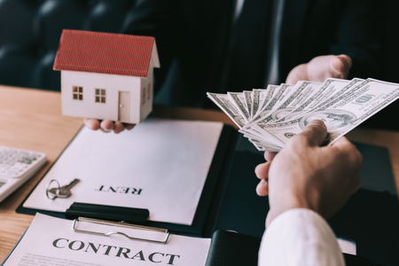 Businessman handed the house model and new homeowner giving money to real estate trading. Reklamní fotografie