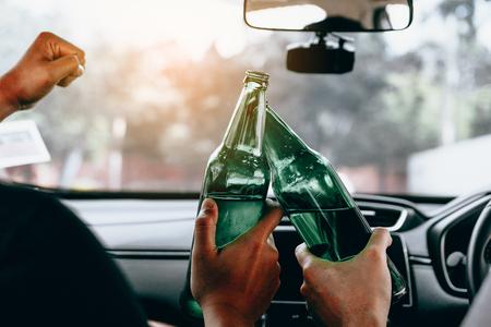 Dos amigos varones están celebrando en el coche mientras tintinean una botella de cerveza juntos.