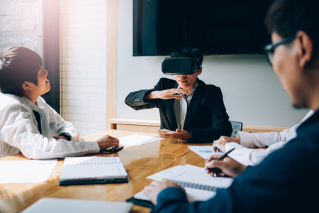 Business team testing virtual reality VR headset technology with colleague in office. Standard-Bild - 120427319