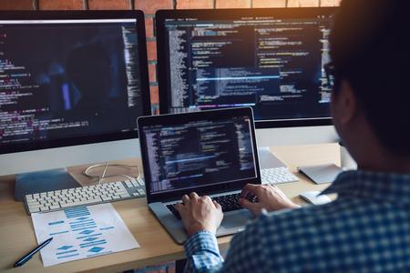 La vue arrière des développeurs de logiciels est assise en analysant sérieusement les données sur l'écran de l'ordinateur.