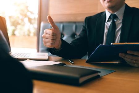 L'intervistatore di lavoro dà un pollice in su per le domande di lavoro per il nuovo dipendente nella stanza dell'ufficio.
