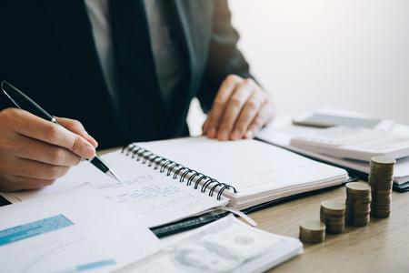 Biznesmeni obliczają koszty sprzedaży firmy i analizują wykres w biurze.