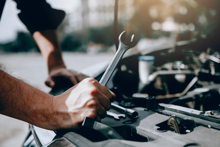 El mecánico de automóviles sostiene una llave lista para revisar el motor y el mantenimiento. Foto de archivo