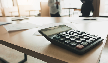 Close up of calculator on desk with business people talking background. Foto de archivo - 120431010