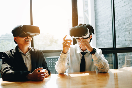 Two business business persons with virtual reality headsets in the office. Foto de archivo - 120431075