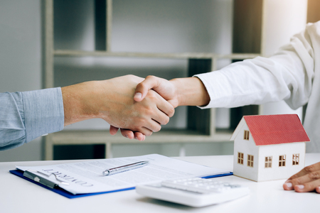Home sales agents and buyers work on signing new homes and shaking hands. Foto de archivo - 120431194