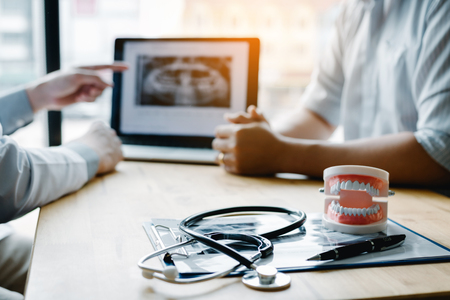 Mano del dentista che indica l'immagine a raggi x nel computer portatile e parla con il paziente del trattamento farmacologico e chirurgico. Archivio Fotografico