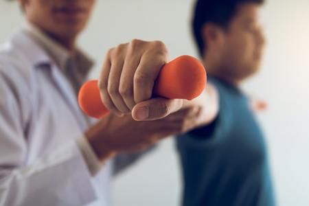 Fisioterapeuta masculino joven asiático que ayuda al paciente con ejercicios de levantamiento de pesas en la oficina.