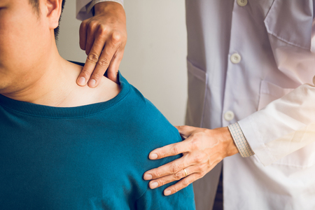 Physical therapists are using their hands to press the clavicle of the patient.