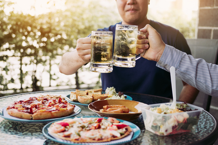 Asian people are socializing outside the house with lots of food on the table and holding a glass of beer inside clinking and enjoy together. Banco de Imagens - 124606935