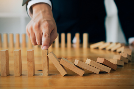 Close up finger businessman stopping wooden block from falling in the line of domino with risk concept. Stock Photo