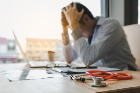 Jonge man arts uitgeput in de kantoorruimte. Stockfoto