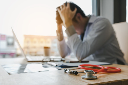Junger Mannarzt, der im Büroraum erschöpft ist. Standard-Bild