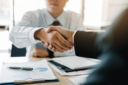 Businessman shaking hands with customer in office. Imagens