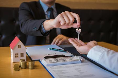 Hausmakler für Verkäufer stellen neuen Hausbesitzern im Büro Schlüssel zur Verfügung.