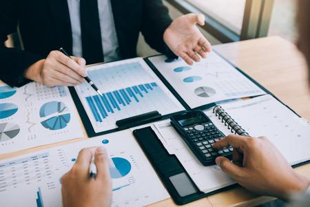 Deux hommes d'affaires parlent de graphique et d'analyse sur l'entreprise budgétaire et utilisent une calculatrice dans la salle de bureau.