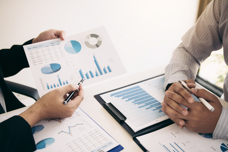 Two business partnership coworkers analysis strategy and gesturing with discussing a financial planning graph and company budget during a budget meeting in office room. Banque d'images