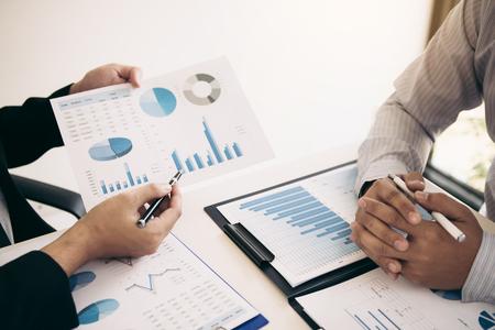 Zwei Geschäftspartner analysieren die Strategie und gestikulieren mit der Diskussion eines Finanzplanungsdiagramms und des Unternehmensbudgets während einer Budgetbesprechung im Büroraum.