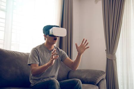 Young asian man wearing virtual reality glasses at living room for admiring virtual reality.