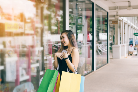 Asian women are happy while holding a paper shopping bag at outlet mall.