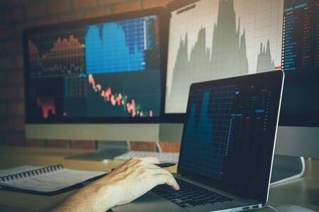 Investors are using laptops entering investment websites stocks market and analyzing performance data.