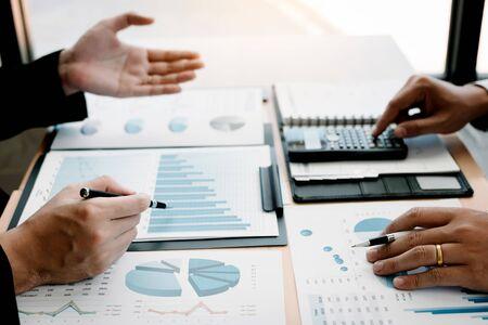 Zwei Geschäftsleute, die über Diagramm und Analyse über Finanzbudgetunternehmen sprechen und Taschenrechner im Büroraum verwenden. Standard-Bild