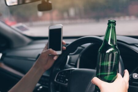 Asian men drink alcohol in the car and using mobile phones while driving.
