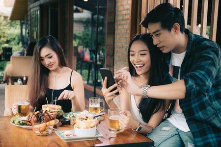 Asiatische alleinstehende Frau neidisch auf Liebespaar, das Selfie im Restaurant nimmt. Standard-Bild