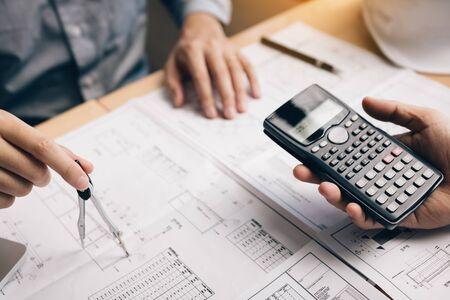 Zwei Architekten, die auf der Baustelle arbeiten, und die Kompasszeichnung, die auf die Blaupause mit dem Taschenrechner zeigt, berechnen.