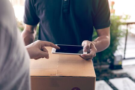 Close up of hand asian man using smartphone pressing screen to sign for delivery from the courier at home. Stock Photo
