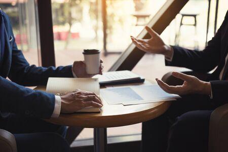 L'analisi di due colleghi di partnership commerciale costa l'avanzamento del lavoro e gesticola con la discussione di un grafico di pianificazione finanziaria e finanziaria dell'azienda durante una riunione di bilancio nella stanza dell'ufficio. Archivio Fotografico