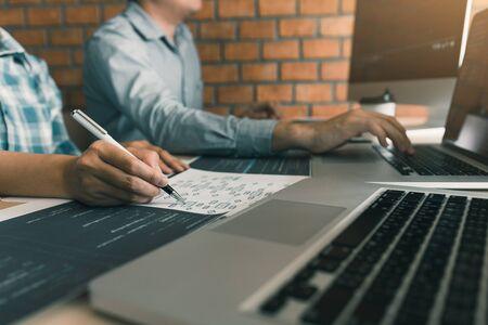Twee softwareontwikkelaars gebruiken computers om samen met hun partner aan het bureau te werken.