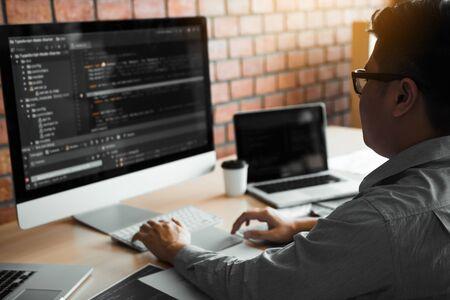 Asiatischer Mann, der Code-Programmentwickler Computer Web-Entwicklung arbeitet, Design-Software auf dem Schreibtisch im Büro.