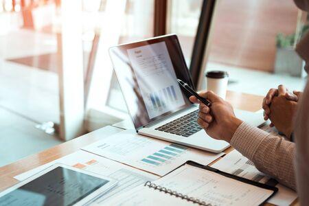 El gerente está usando una computadora portátil mientras analiza los estados financieros de la empresa en la pantalla.