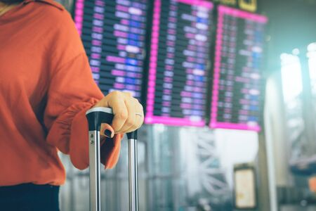 Young asian woman standing at the airport holding suitcase checking departure with the flight schedule in background.