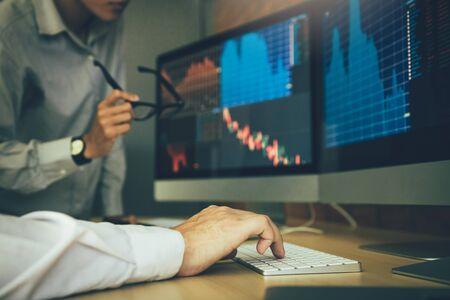 Dos corredores de bolsa de negocios estresan y miran monitores que muestran información financiera.