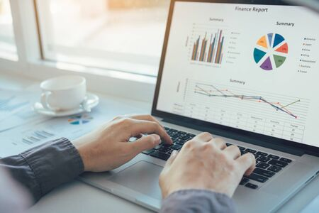 Investors are using laptop computers to analyze graphs in the morning. Banco de Imagens