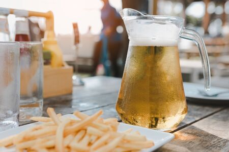 A pitcher of Singha beer with a glass of beer on the table.