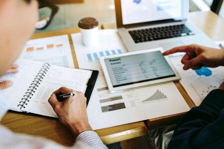 Współpracownicy w ramach partnerstwa biznesowego analizują postęp prac kosztowych i używają tabletu do sporządzania raportów finansowych firmy i planowania na przyszłość w pomieszczeniu biurowym.