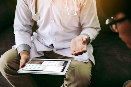 Asian doctor visited the patient at home while using the tablet explaining the patient condition and the treatment result.
