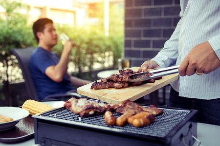 Asian men are pinching pork on a wooden cutting board and holding it to friends who are celebrating in the back.