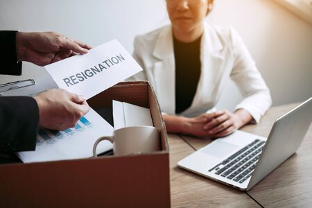 Male employee takes the handle to the resignation envelope while being handed over to the female manager.
