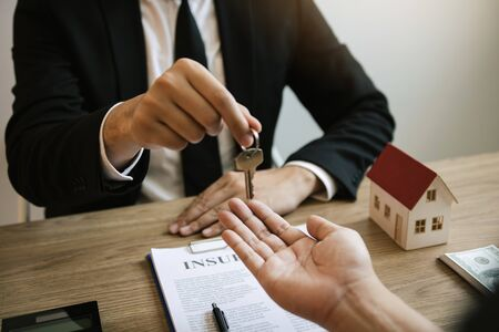 Home agents are handing out keys to home buyers who are signing contracts at the office. Banco de Imagens